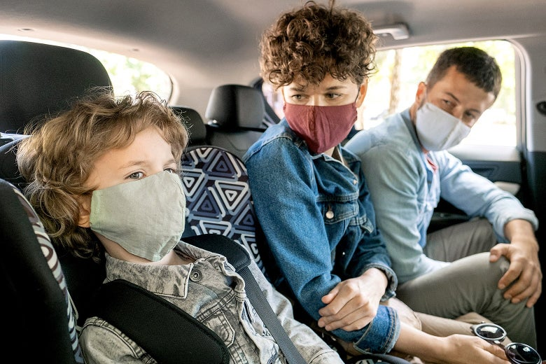 Masked kids in the back seat of a car.