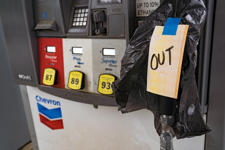 """At a gas pump, the handle is covered with a trash bag that says """"OUT."""""""