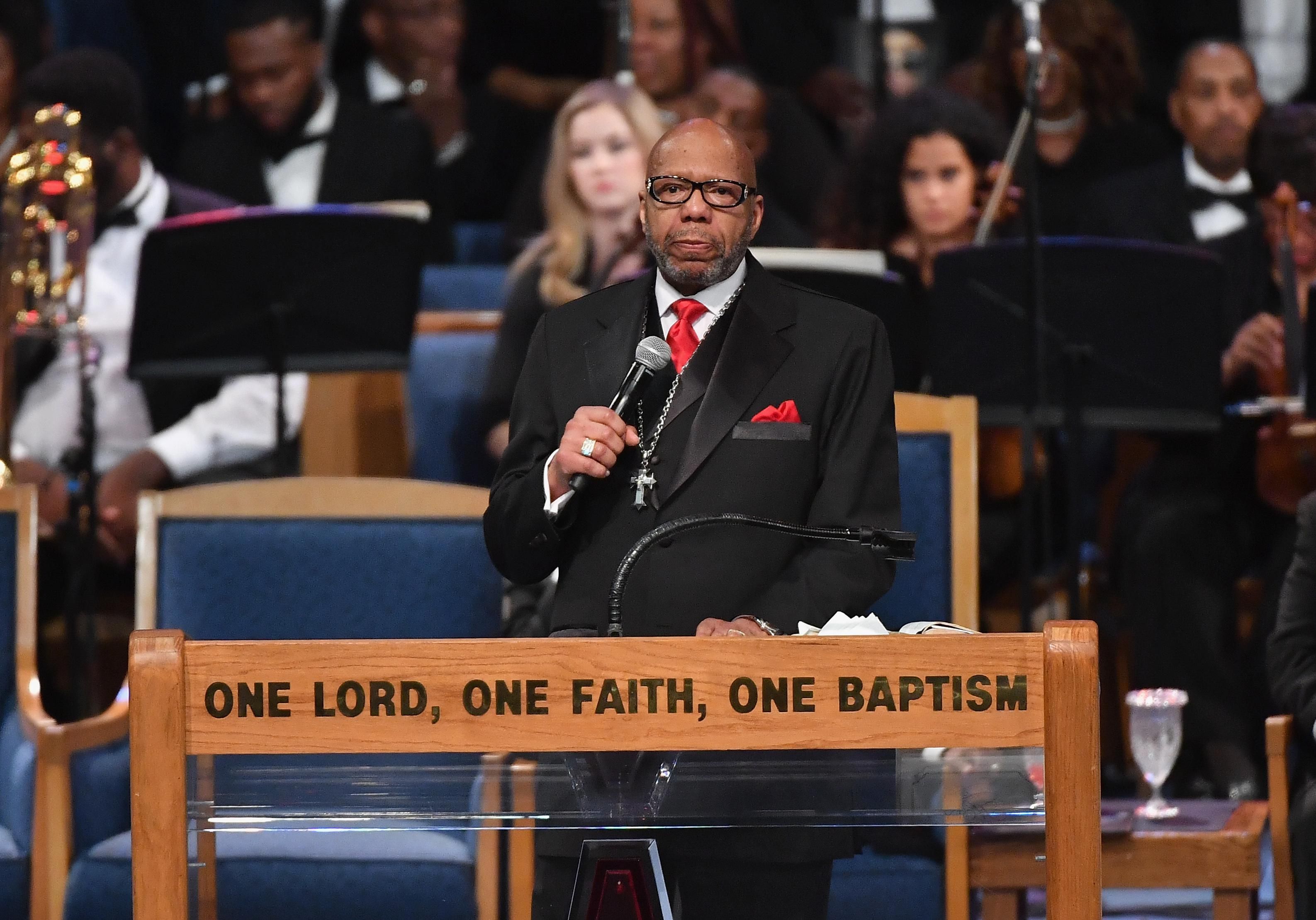 Rev. Jasper Williams Jr. stands on a pulpit with the engraving ONE LORD, ONE FAITH, ONE BAPTISM.