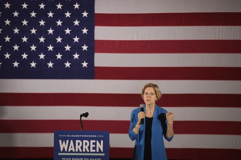 Warren, wearing blue, speaks in front of a blue lectern with a WARREN sign on it and a large American flag backdrop.