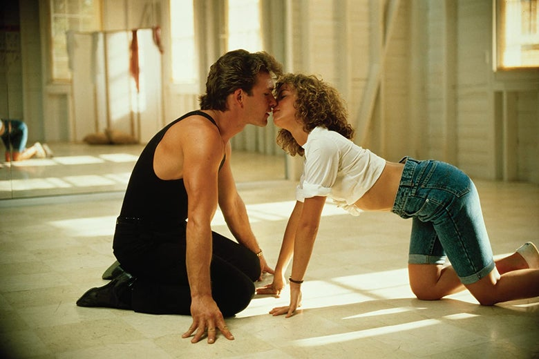 Jennifer Grey and Patrick Swayze almost kissing on the floor of a dance studio.