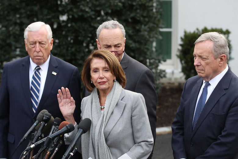 Pelosi speaks as the three men watch her in what appears to be a White House driveway.