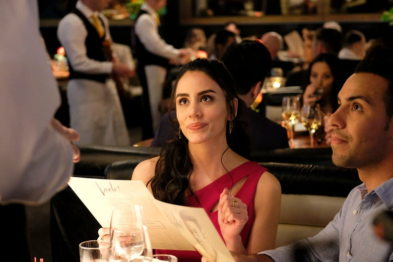 A woman wearing a red dress looks up at a waiter, a menu in hand. She sits next to a man in a button-down shirt.