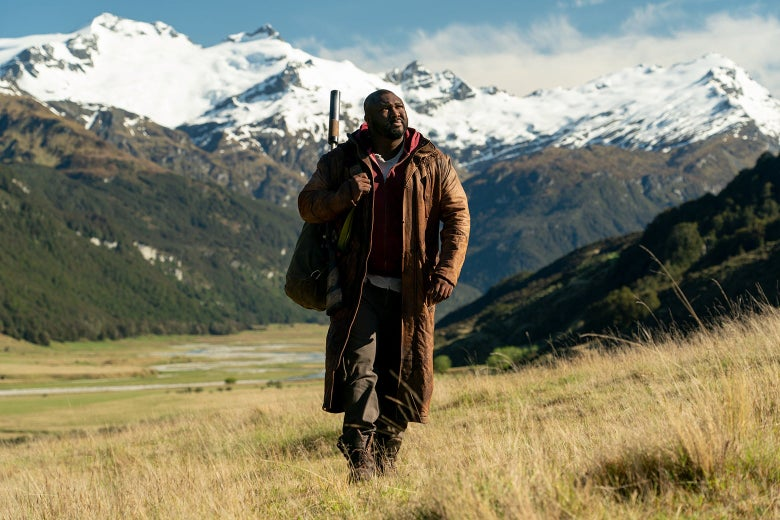Nonso Anonzie walks across a golden meadow, with whitecapped mountains in the background. He is wearing a long leather coat and has a rifle strapped to his back.