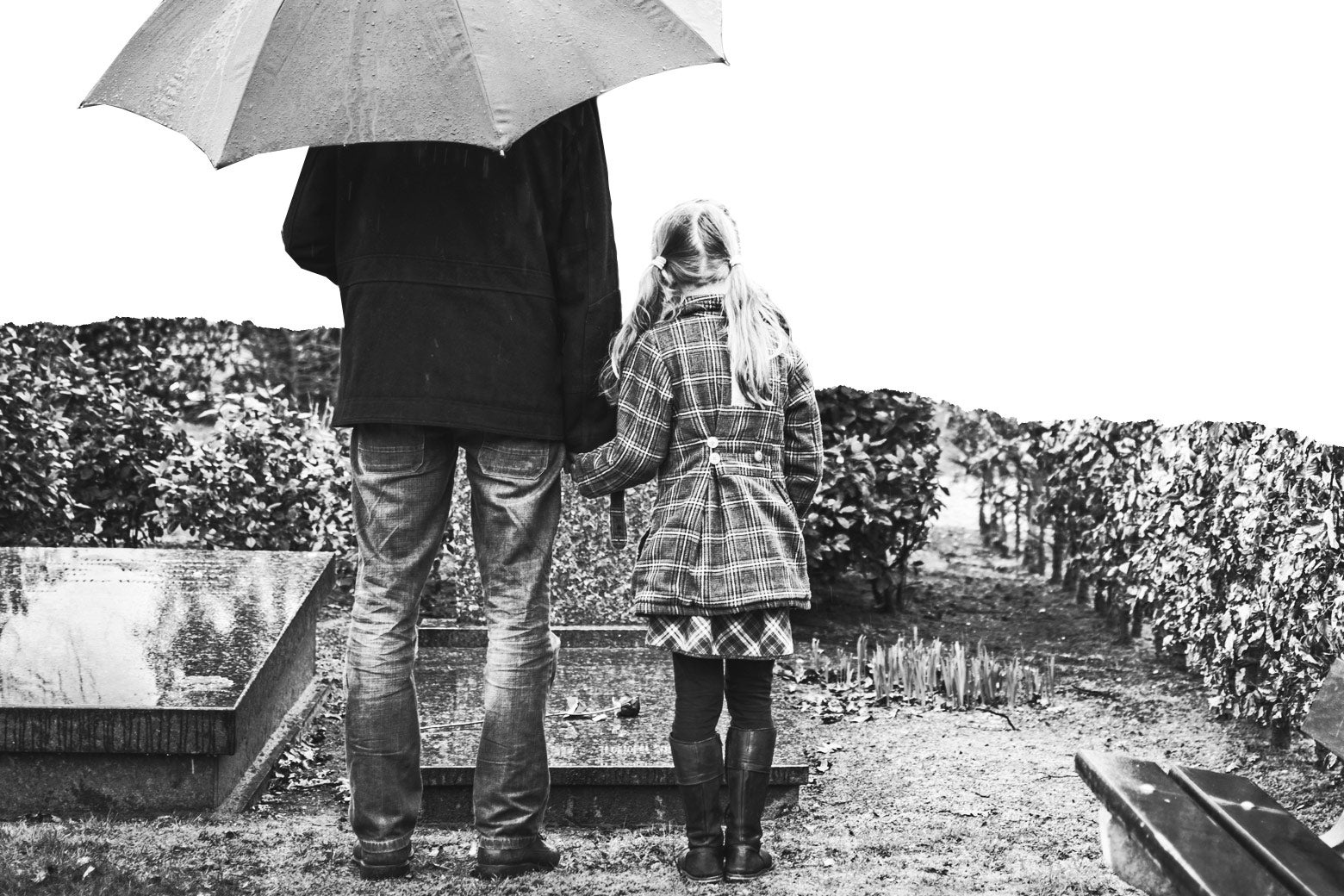A father and daughter stand over a grave in the rain.