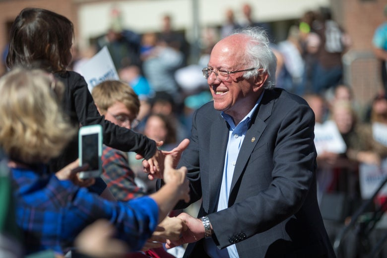Sen. Bernie Sanders shakes hands with supporters at an outdoor campaign event.