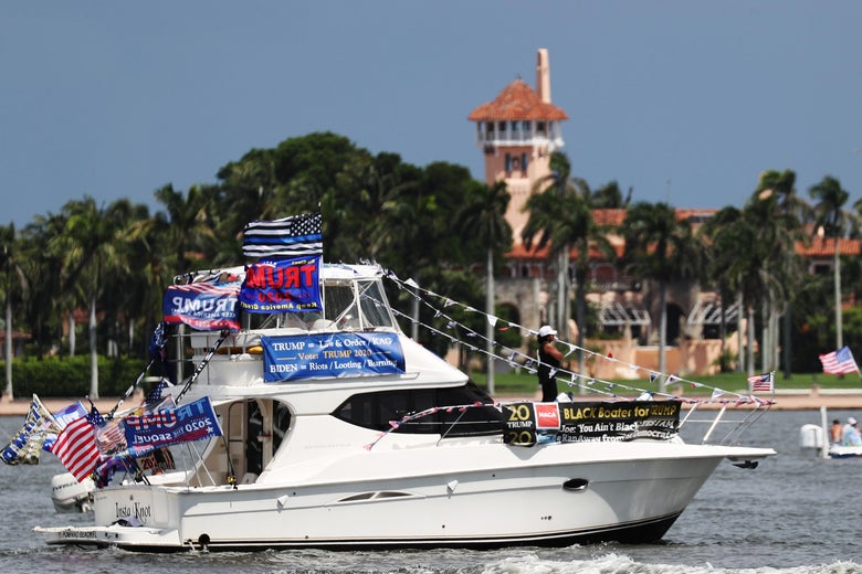 A boat draped in Trump banners sails past Mar-a-Lago.