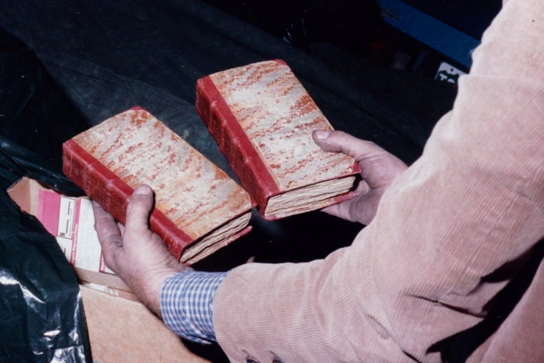 A man holds two ancient-looking books.