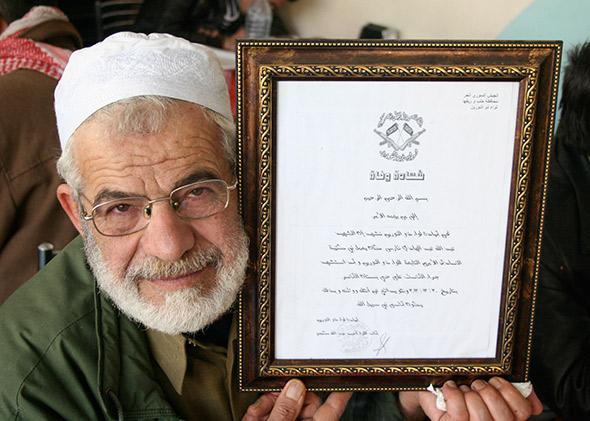 Abu Yaseen holding his son's martyrdom certificate.