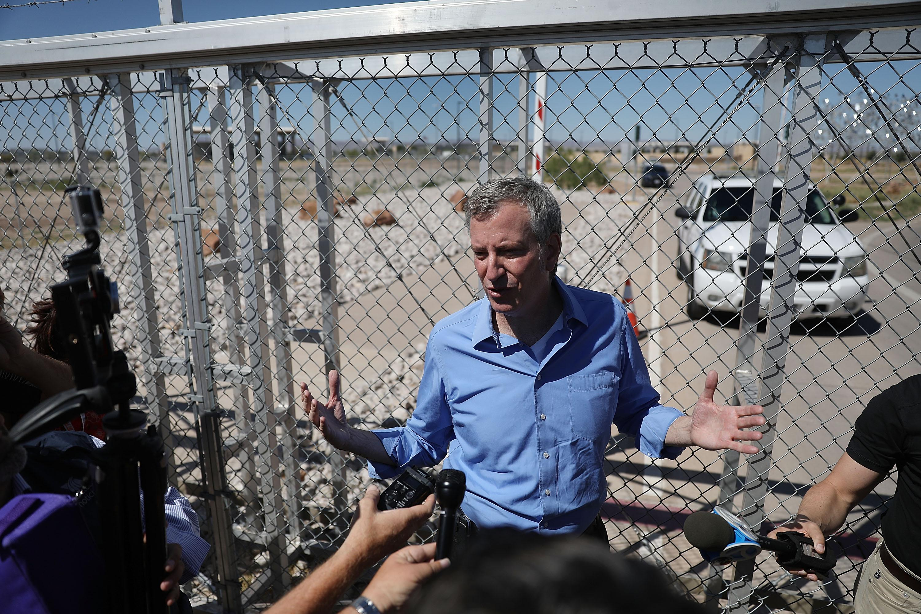 New York City Mayor Bill de Blasio speaks with the media in front of a gate at the port of entry.