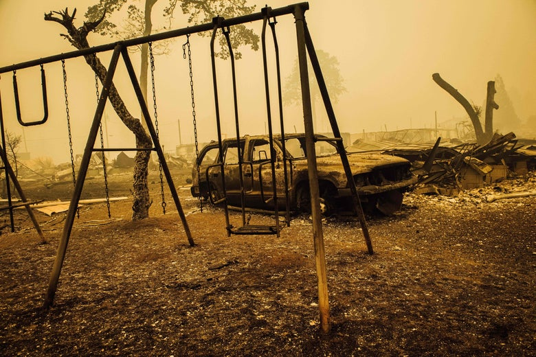 A charred car and swing set in a burned-out landscape yellow with smoke.