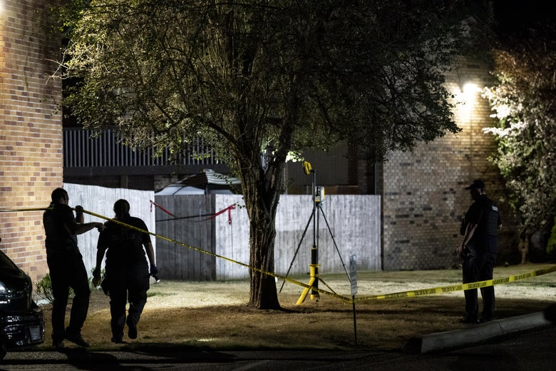 Three officers walk around a crime scene, marked by yellow tape. The scene appears to be outside an apartment building and around a tree.