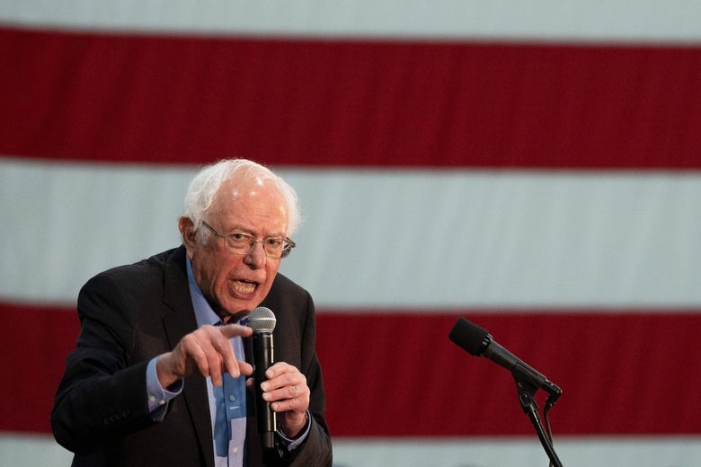 Bernie Sanders, standing in front of an American flag, speaks into a microphone.
