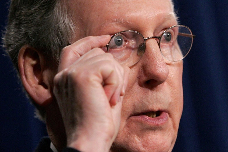 A close-up of Mitch McConnell's face, in which he puts his hand to his glasses