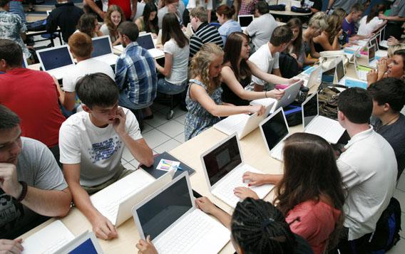 Students set up their donated laptop computers on the first day of school at Joplin High School in Joplin, Missouri.