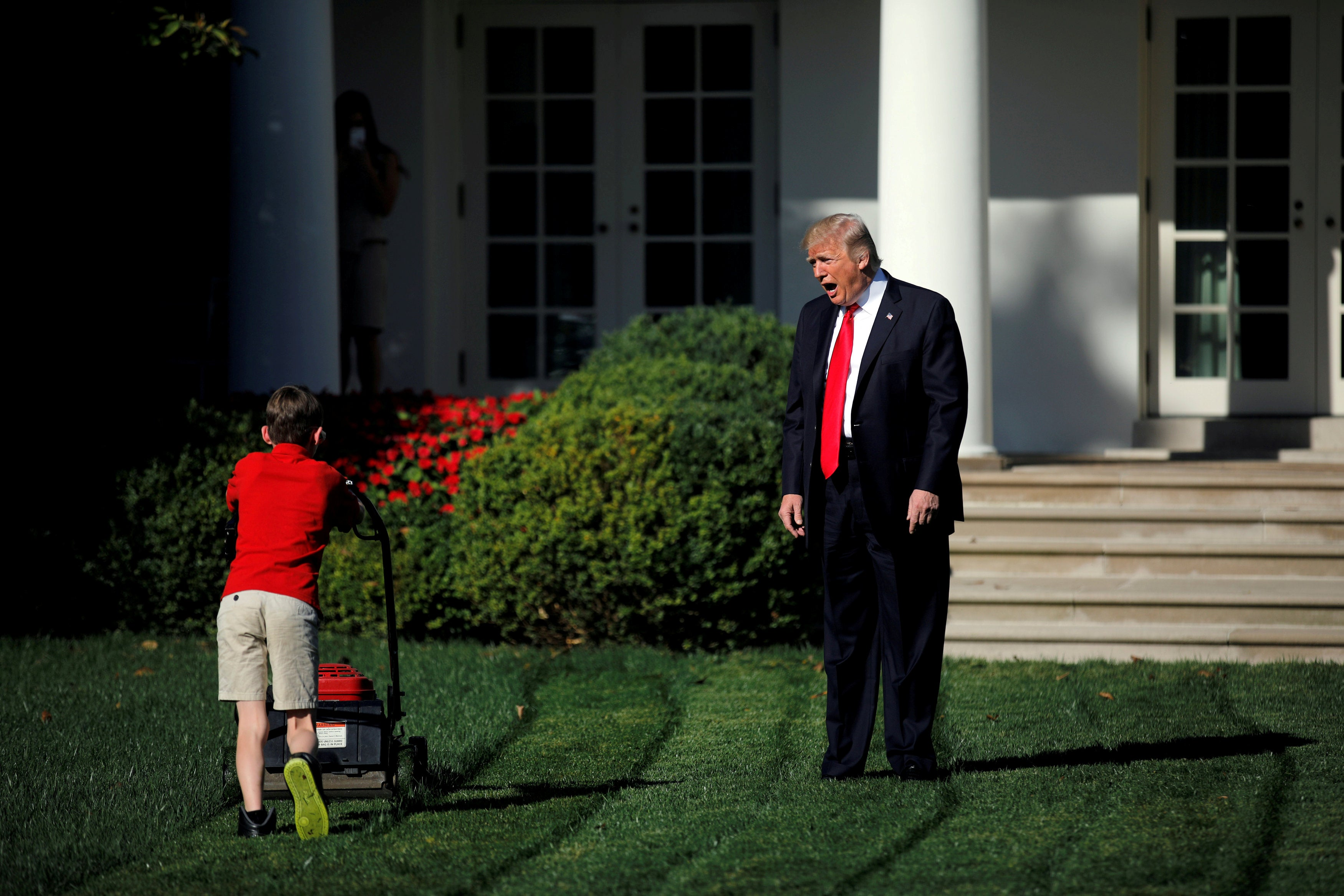 Trump, with his hands at his sides, speaks toward a small boy in a red shirt who is mowing the White House lawn.