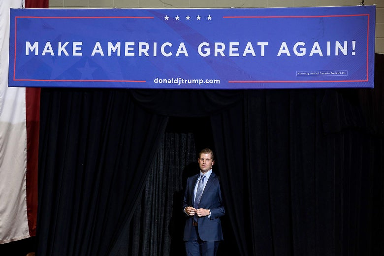 "Eric Trump stands in the wings of a stage with a ""Make America Great Again"" sign over him."