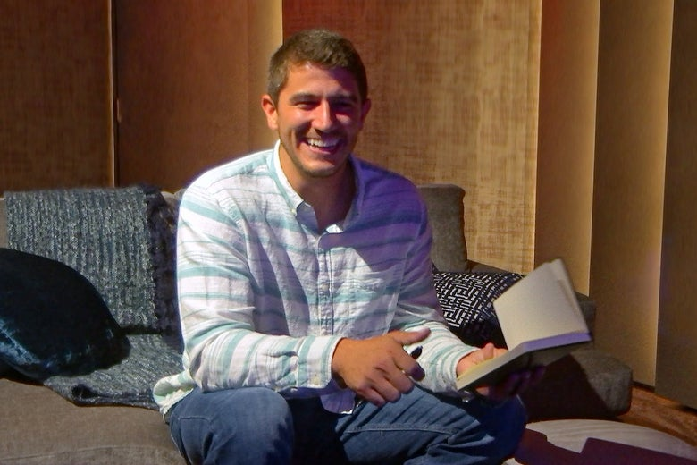 Love Is Blind's Barnett sits on couch with a book in his hand smiling at the camera.