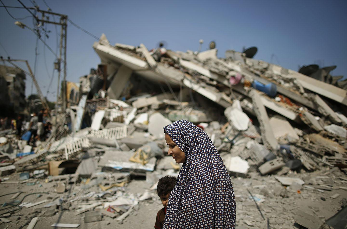 A Palestinian woman walks past the rubble of a residential building.