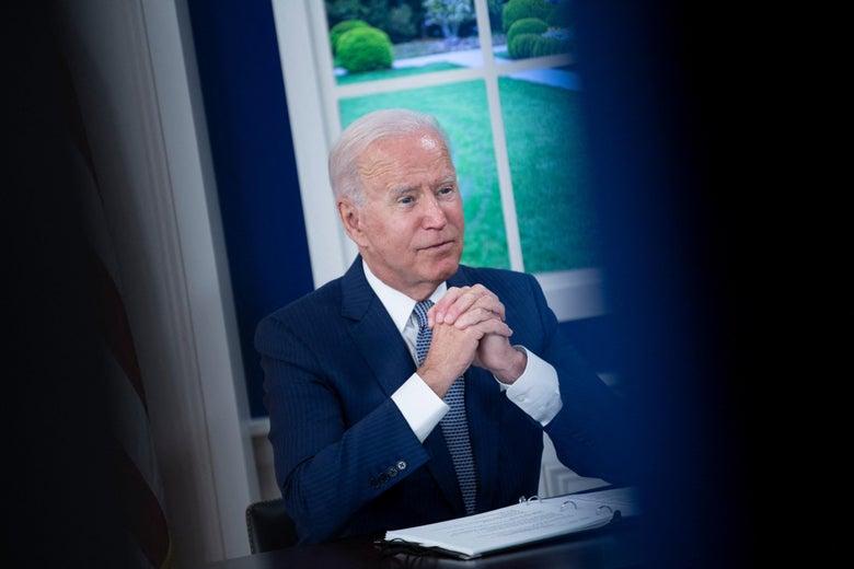 Joe Biden sits at a desk with hands near his chin.