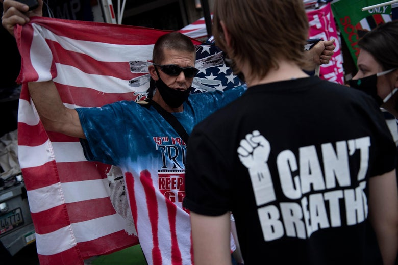 A Trump supporter and Black Lives Matter protester talk before a rally with US President Donald Trump later at the BOK Center on June 20, 2020, in Tulsa, Oklahoma.