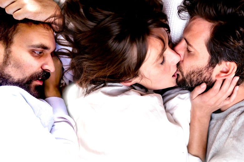 Two men in bed with a woman, one kissing her, the other looking on nervously.