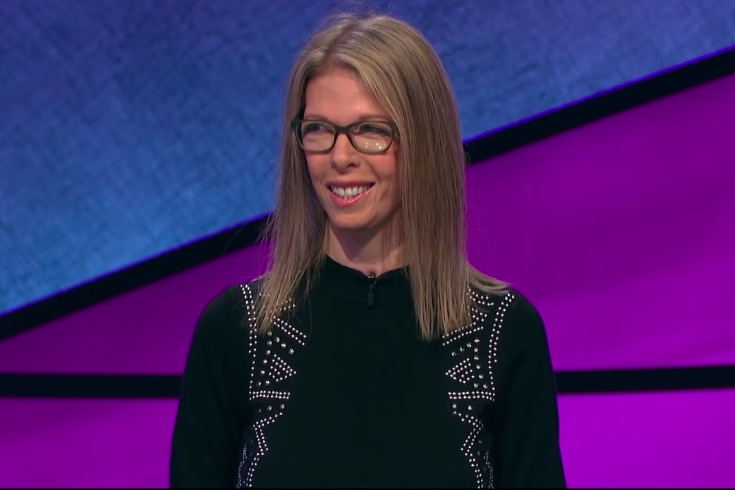 Jackie Fuchs stands in front of a blue and purple Jeopardy! backdrop, smiling in glasses and a black shirt.