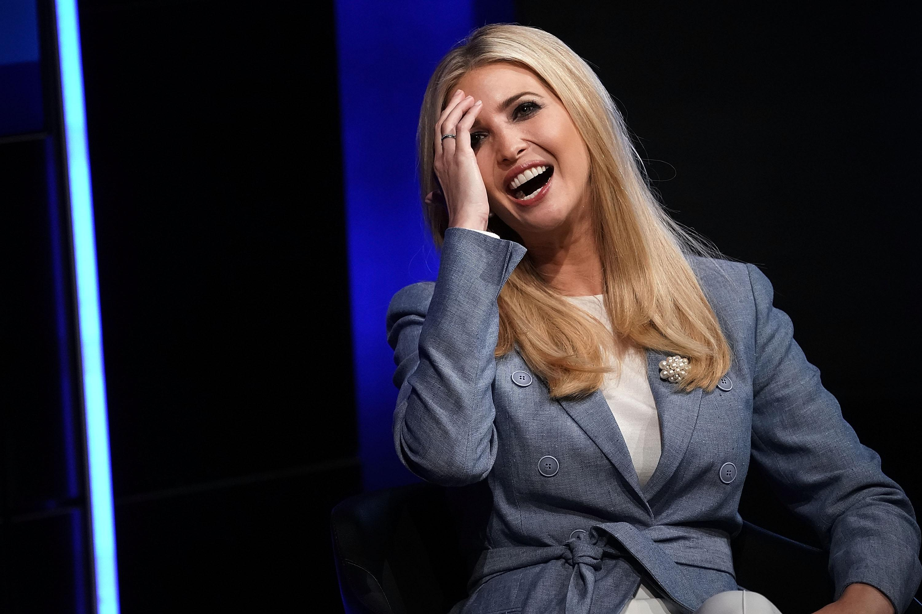 Ivanka Trump laughs as she pushes her hair back out of her face.