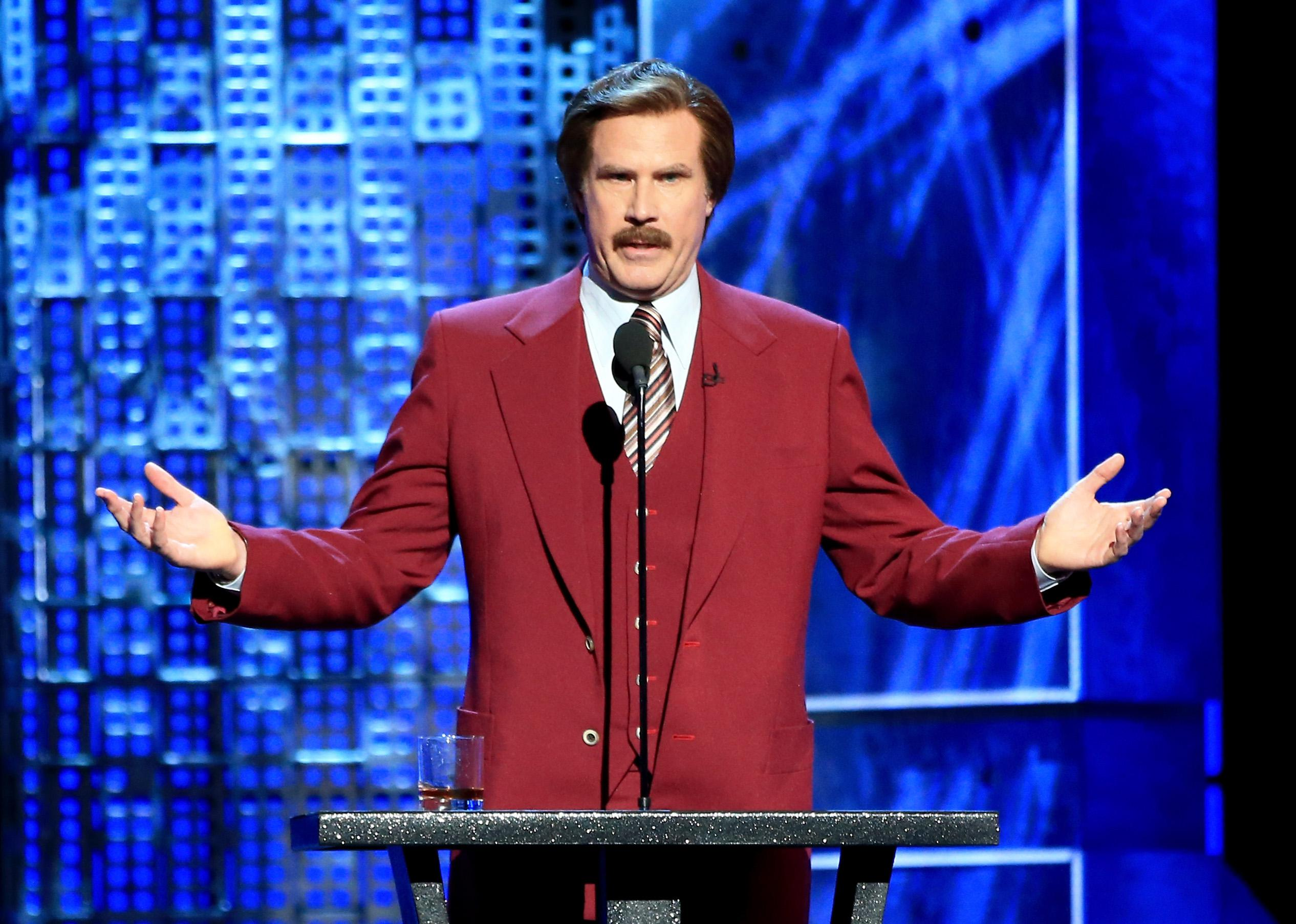 Will Ferrell stands at a podium, arms raised, wearing his Ron Burgundy red suit and mustache.