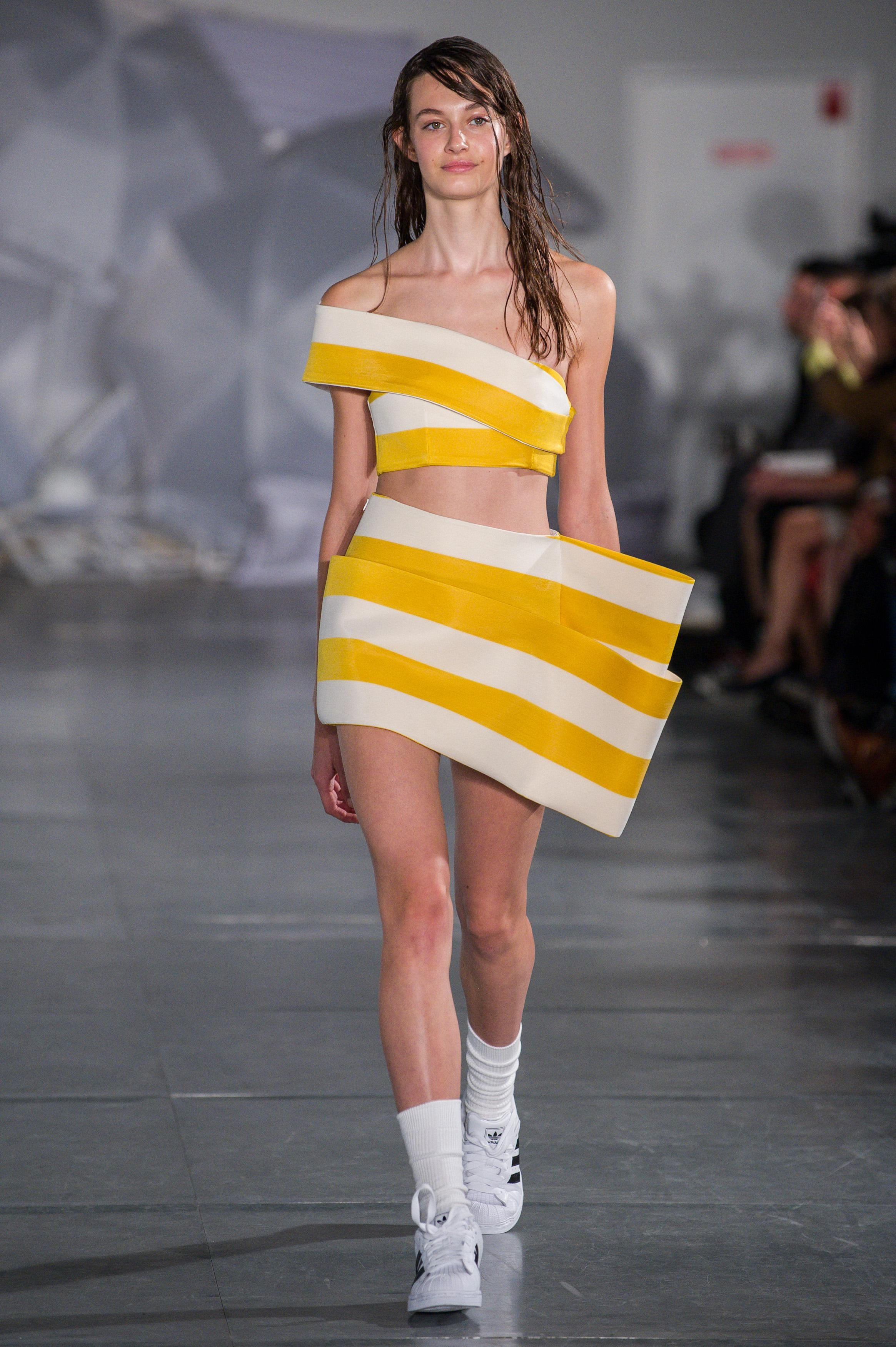 A model walking the runway with wet hair.