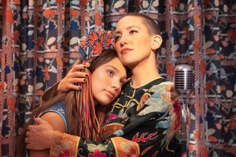 In front of a patterned curtain, Kate Hudson, with close-buzzed hair, embraces Maddie Ziegler. A microphone stands next to them.