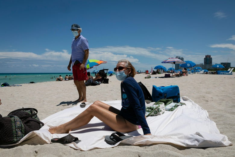 a woman on a beach blanket with a mask