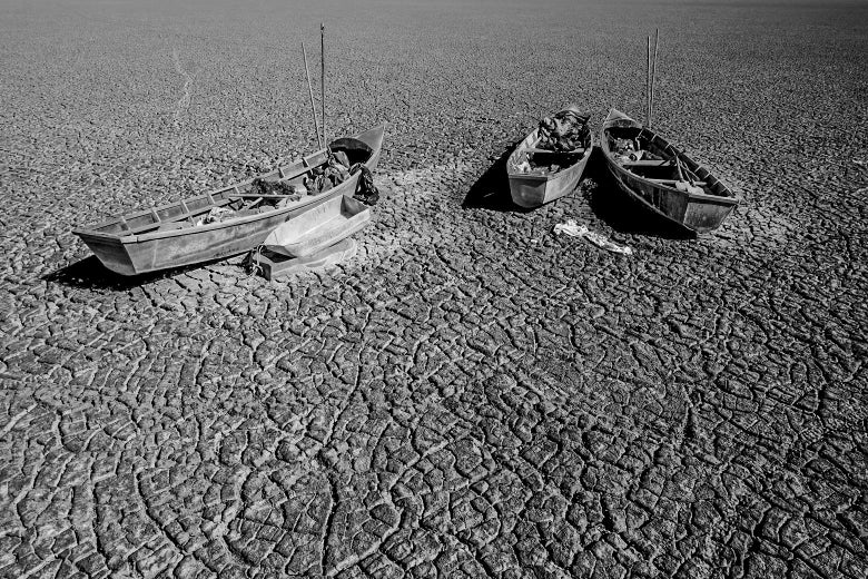 Boats of fishermen are seen on the dried Poopo lakebed in the Oruro Department, south of La Paz, Bolivia, December 17, 2015. Lake Poopo in Bolivia, the Andean nation's formerly second largest after the famed Titicaca, has dried up entirely. With the water now gone, animals have died off in the millions, according to studies. And the local families, having lost much of their sustenance, have been forced to migrate. REUTERS/David Mercado