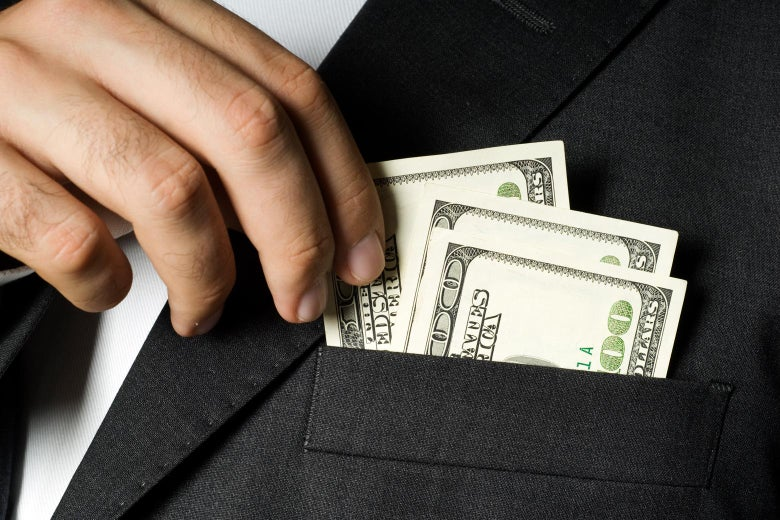 A person puts $100 bills in a suit pocket.