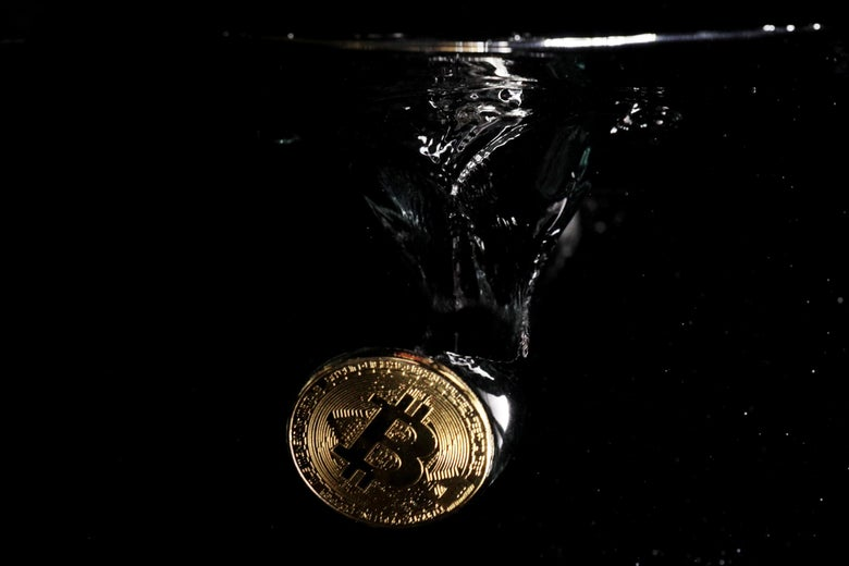 A bitcoin symbol submerged in water.