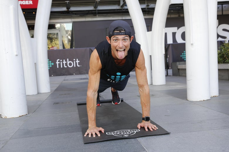A man sticks his tongue out while doing a plank.