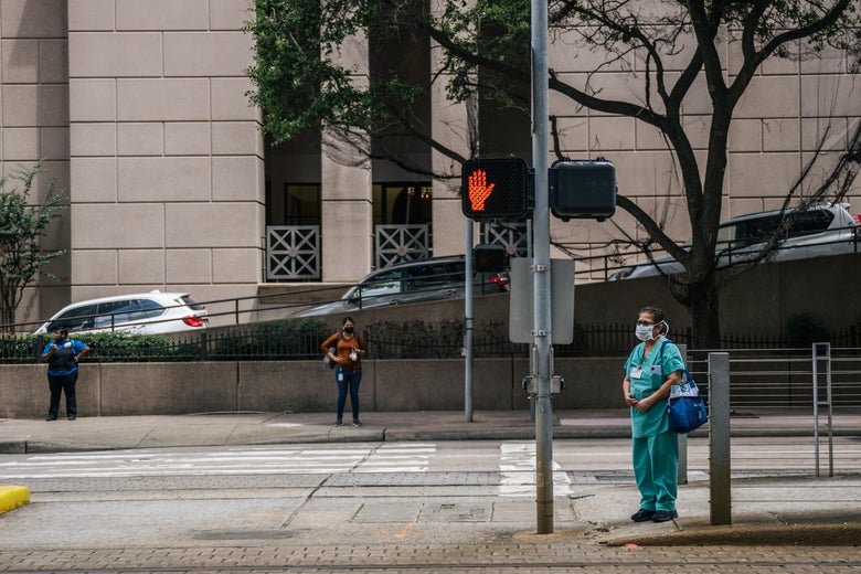 A nurse and pedestrians wait to cross an intersection outside of the Houston Methodist Hospital on June 09, 2021 in Houston, Texas. Houston Methodist Hospital has suspended 178 employees without pay for 14 days for their refusal to comply with its COVID-19 vaccine requirement.