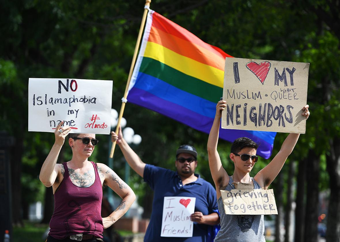 Lynne Sprague, left, Jeremy Bermudez, in back in middle, and Andy Coco, right,  who are all part of the Denver LGBTQ community, show their support for the muslim community  at the corners of Broadway and Colfax on June 12, 2016  in Denver, Colorado.