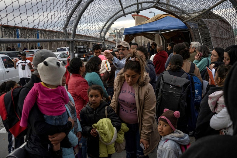 A crowd of women and kids walk across a bridge.