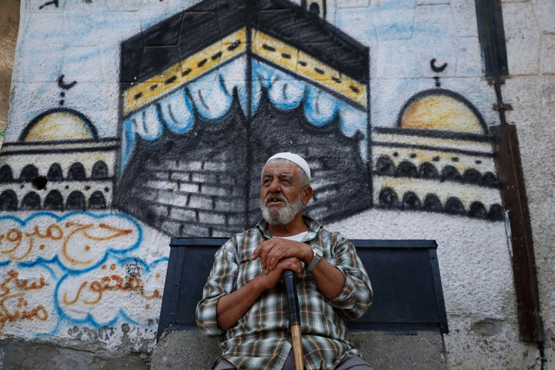 An elderly Palestinian man sits in front of a mural depicting the Kaaba.