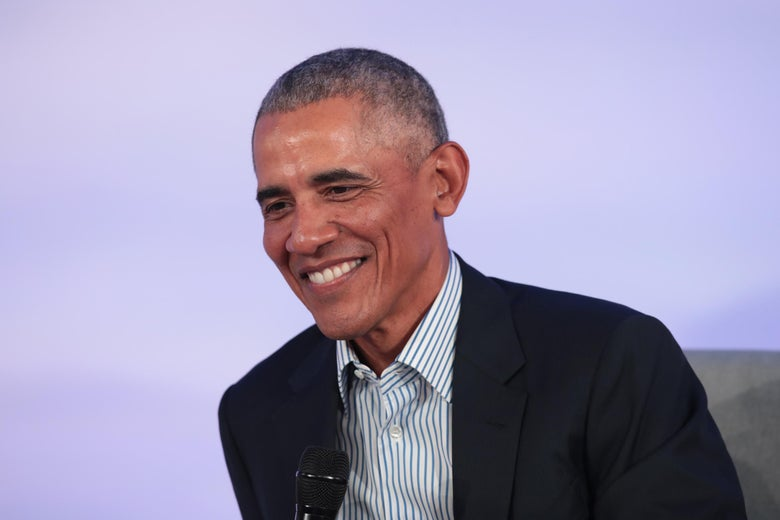 Barack Obama in a striped shirt and suit jacket, smiling.