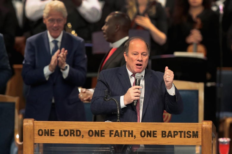 """Mike Duggan stands on a pulpit with the words """"One Lord, One Faith, One Baptism"""" on it."""