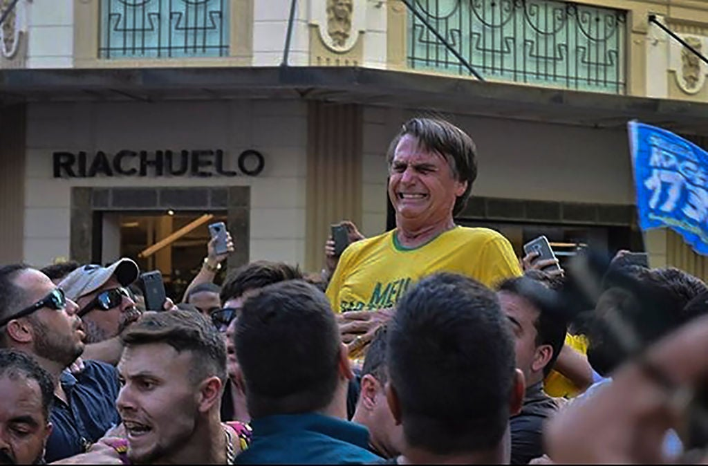Bolsonaro, wearing a yellow t-shirt, reacts in the midst of a large crowd.