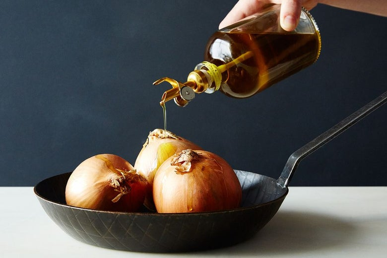 A hand pours olive oil over three unpeeled onions in a skillet.