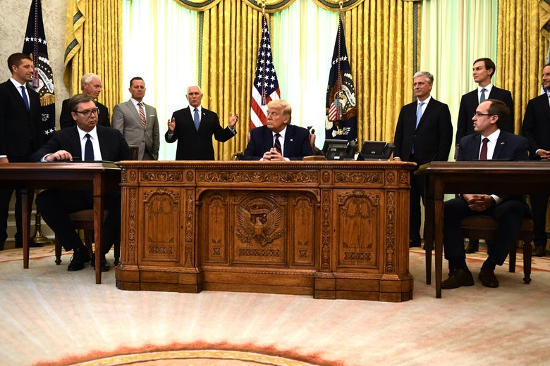 U.S. President Donald Trump, Kosovar Prime Minister Avdullah Hoti, and Serbian President Aleksandar Vucic, and U.S. Vice President Mike Pence sit with other politicians in the Oval Office.