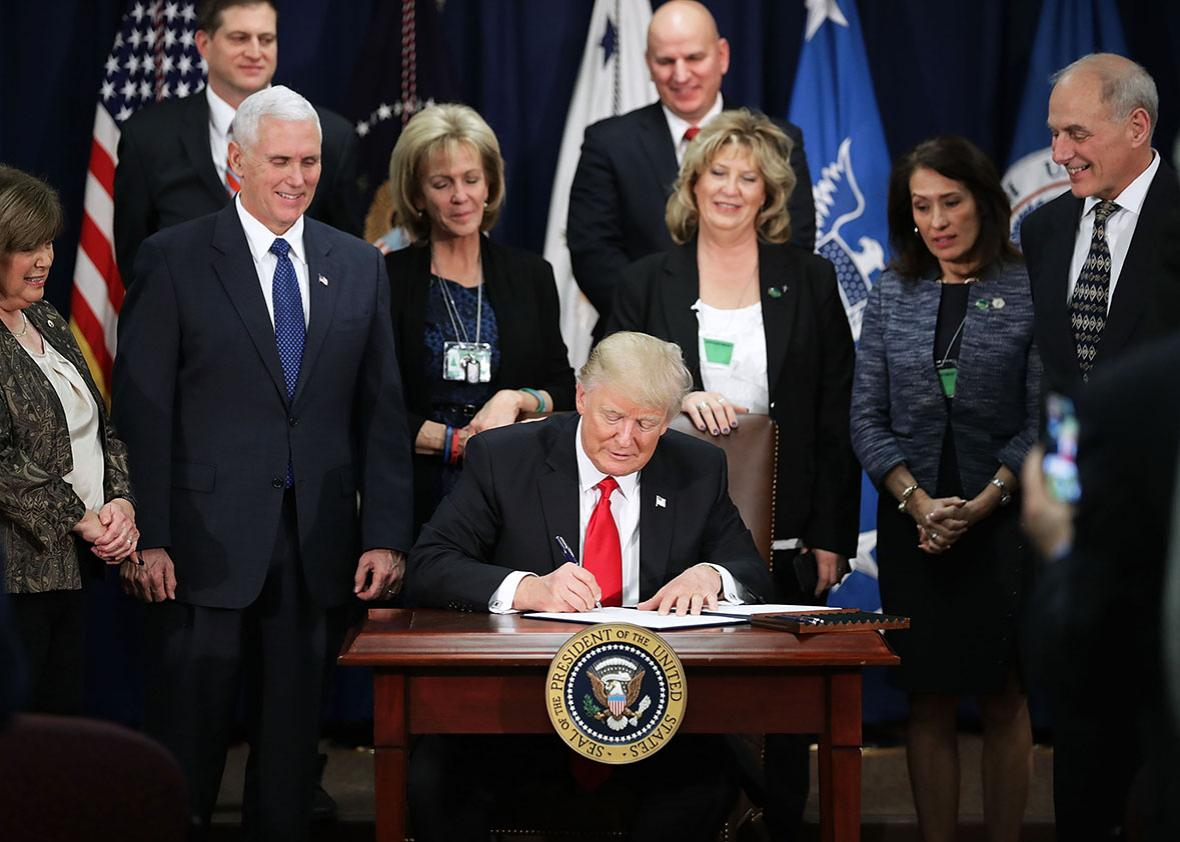 U.S. President Donald Trump signs four executive orders during a visit to the Department of Homeland Security with Vice President Mike Pence, Homeland Security Secretary John Kelly and other officials January 25, 2017 in Washington, DC.