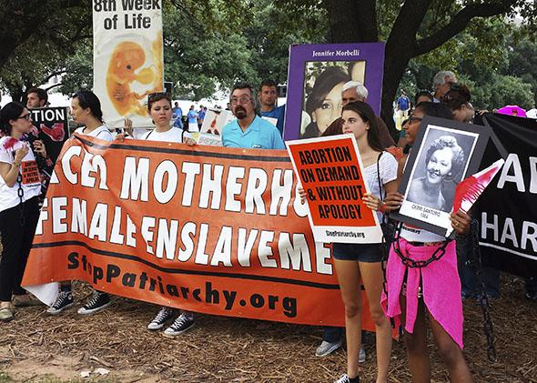 Abortion rights activists protest outside a U.S. federal court in Austin, Texas August 4, 2014 where a hearing started to hear a case by the Center for Reproductive Rights against a new set of restrictions on abortion clinics in the state that went into effect in September.