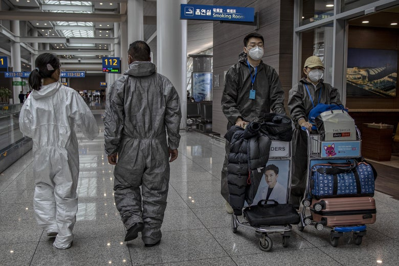 People wearing protective suits and face masks walk in the airport