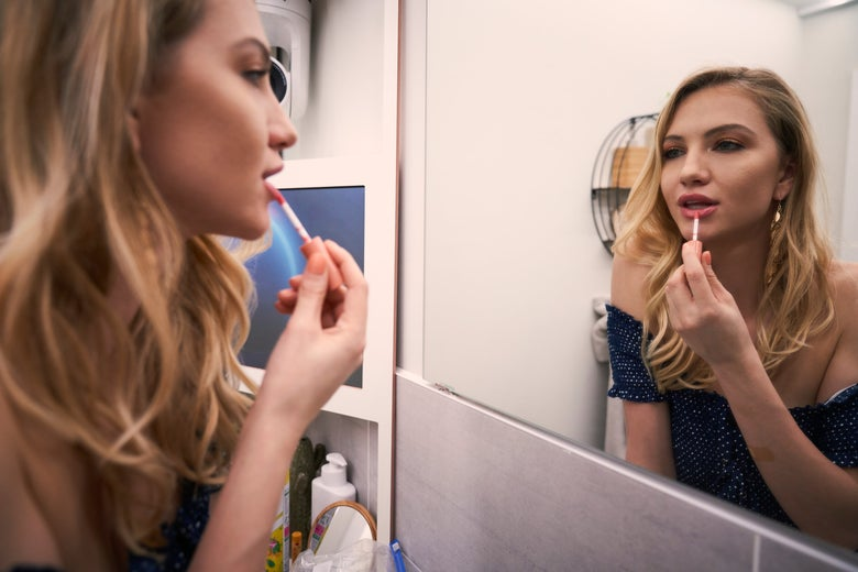 A woman looks at herself in the mirror while applying lip gloss.