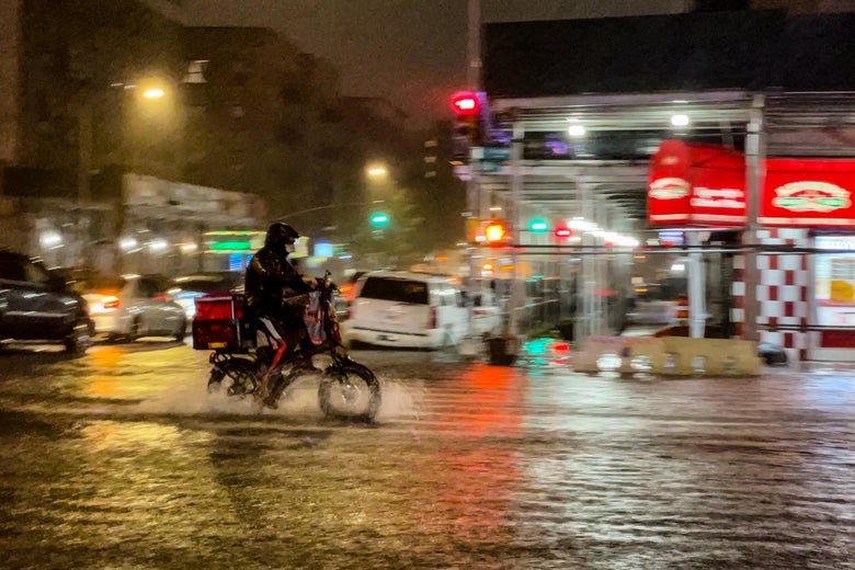 A delivery worker makes their way in the rainfall from Hurricane Ida during a flood on Intervale Avenue on September 1, 2021, in the Bronx borough of New York City.
